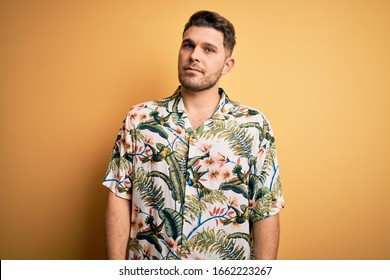 Young man with blue eyes on vacation wearing floral summer shirt over yellow background Relaxed with serious expression on face. Simple and natural looking at the camera.