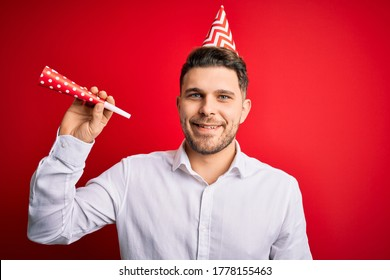 Young man with blue eyes wearing birthday cap and holding festive trumpet with a happy face standing and smiling with a confident smile showing teeth