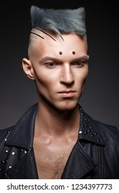 young man with blue hair and creative makeup and hair. Photo taken in the studio