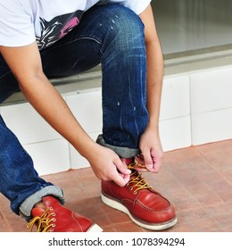young man with blue jean and brown leather shoes.