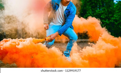 a young man in a blue jumpsuit and a white T-shirt is holding a smoke bomb in his hands. A man is holding colored orange smoke