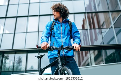 Young man in blue raincoat standing with his bike after cycling in the street on a rainy day. Curly male courier in blue raincoat delivers parcel cycling with a bicycle.
