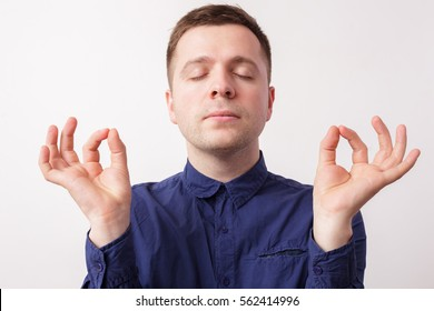 Young man in a blue shirt, breathing deeply, trying to calm down. Fingers together, his eyes covered
