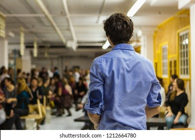 Young Man with blue shirt is giving a conference in front of 200 people in an industrial environment with yellow and white walls - Blurred audience mainly composed of young adults