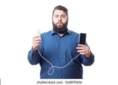 Young man with blue shirt holds a smartphone and the charger isolated on white background