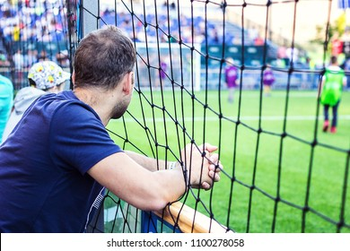 Young man in blue shirt looking at stadium watch soccer match training, standing behind football field fence for protect the ball, with hands on nets. Young people play football field pitch fans.