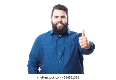 Young man with blue shirt making a gesture of approval isolated on white background