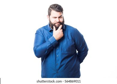 Young man in blue shirt making a thoughtful or sexy gesture touching his chin isolated on white background