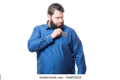 Young man with blue shirt puts a smartphone in his pocket isolated on white background