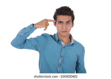 A young man in a blue shirt putting a finger on head thinking, isolated on a white background.