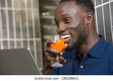 young man in blue shirt sitting near a wall smiling smile with a glass of juice near the mouth.