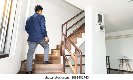 A young man in a blue shirt is walking up the stairs in the building.