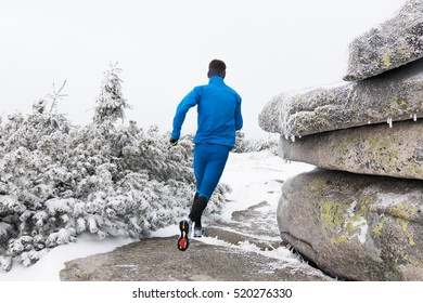 young man in blue sportswear running on the frozen trail in the mountains with snow