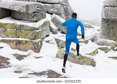 young man in blue sportswear running on the rocky trail in winter mountains with snow