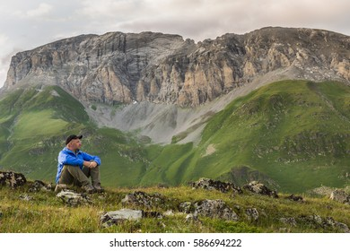 Young man in blue sportswear sits on a hill on a background of rocky mountains. Adventure concept lifestyle