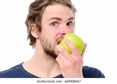 Young man in blue tshirt biting big green apple, looking astonished. Isolated on white background