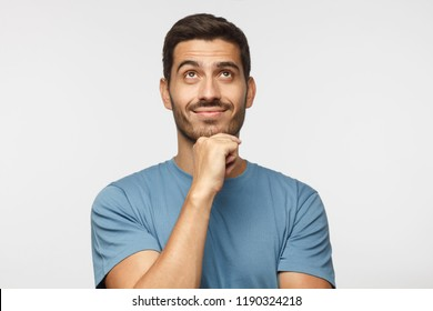 Young man in blue t-shirt with dreamy cheerful expression, thinking, looking up, isolated on gray background