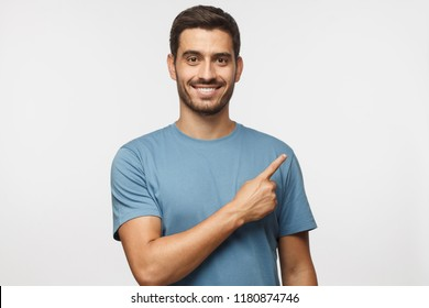 Young man in blue t-shirt pointing right with his finger isolated on gray background