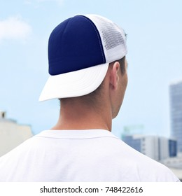 Young man in a blue and white trucker hat, and white t-shirt. Blue baseball cap mockup. Close-up