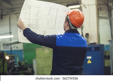 Young man with blueprints working on an old factory for the installation of equipment protective helmets