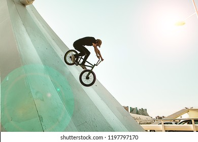 Young man with a bmx bike riding down the street and doing tricks
