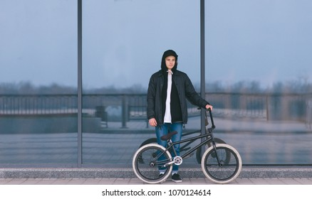 A young man with a BMX bike stands on the background of a dark wall. Portrait of BMX rider. Street culture.