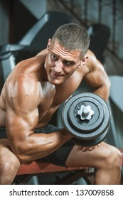 young man bodybuilder doing workout with heavy dumbbell  at gym