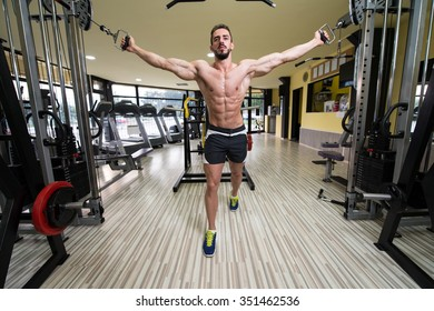 Young Man Bodybuilder Is Working On His Chest With Cable Crossover In A Gym