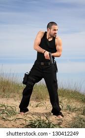 young man bodyguard with a gun outdoor