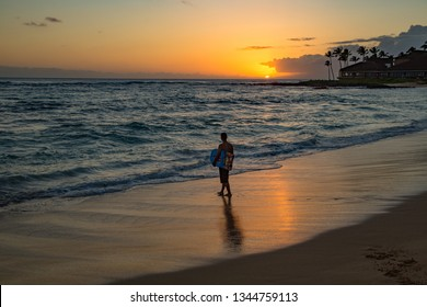 A young man with boogie board at sunset on the wet sand on Poipu beach, Kauai, Hawaii
