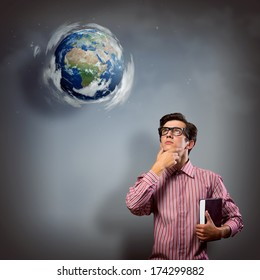 young man with a book thinks. it over planet Earth with clouds. an image of NASA.