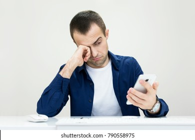 young man bored looking at smart phone, office worker, front view, isolated, background
