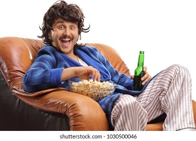 Young man with a bowl of popcorn and a bottle of beer sitting in a leather armchair isolated on white background