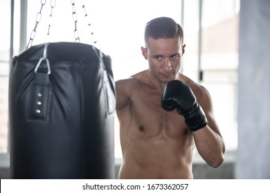 young man with boxing gloves, exercise in fitness gym