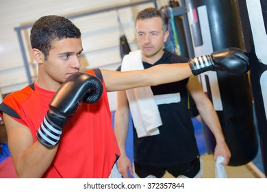 Young man in boxing training with instructor