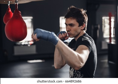 Young man boxing workout in a fitness club. Muscular strong man on background boxing gym.