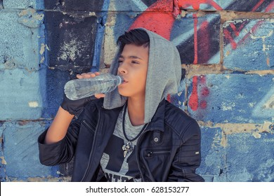 Young man boy skater drinking water over graffiti art urban wall background