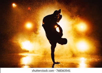 Young man break dancer dramatic silhouette standing on hand in club with lights and water. Tattoo on body.