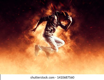Young man break dancing on fire background