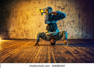 Young man break dancing on wall background. Vibrant blue and red colors effect.