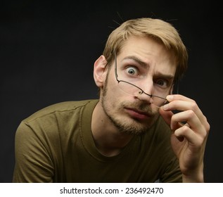 Young man bringing down h is glasses to analyze and inspect something closely