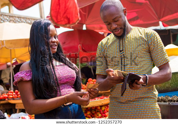 young man bringing out money from his wallet to give to a woman in a local african market