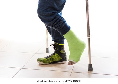 Young man with a broken ankle following a basketball accident, walking on crutches with a modern high-top basketball shoe and a matching yellow - green cast (isolated on white)