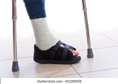 Young man with a broken ankle and a white cast and cast shoe (sandal) on his leg, walking on crutches (isolated on white)