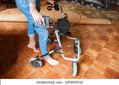 a young man with a broken and deformed leg is standing with a walker on the floor in his room. rehabilitation of victims in hostilities after injuries concept. problem of disabled veterans