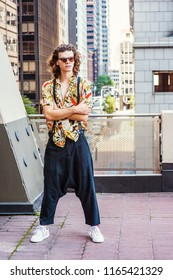 Young Man with brown curly hair, wearing sunglasses, patterned short sleeve shirt, baggy loose pants with suspenders, patterned sneakers, hanging old key as necklace, standing on balcony in New York.
