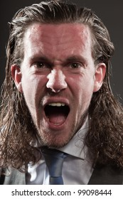 Young man brown long hair with expressive face wearing grey suit and blue tie. Isolated on grey background. Screaming. Anger. Aggressive.