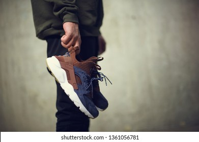 Young man with brown Nike Air Huarache sport shoes in hand shot on grey background. Nike sneakers, trainers close up view. Sport and casual footwear concept. Krasnoyarsk, Russia - January 10, 2018