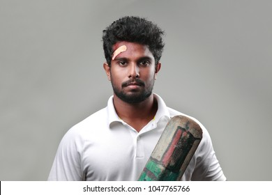 Young man with a bruised forehead holding cricket bat