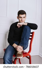 young man brunette sitting on a coloured chair. posing in a photo Studio. emotional portrait. short hair and clean skin on the face